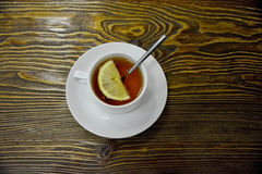 Cup of tea with lemon. Cup of tea served with lemon, on wooden background. Shot made from above Stock Photography