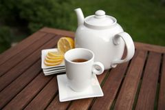 Cup of tea lemon slices and bowl. On table in the garden Royalty Free Stock Photos