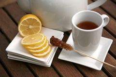Cup of tea lemon slices and bowl. On table in the garden Stock Photo