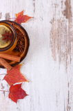 Cup of tea with lemon, spices and autumnal leaves on wooden background, copy space for text Royalty Free Stock Photo