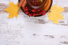 Cup of tea with lemon, spices and autumnal leaves on wooden background, copy space for text Royalty Free Stock Image