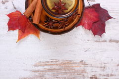 Cup of tea with lemon, spices and autumnal leaves on wooden background, copy space for text Stock Photos