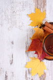 Cup of tea with lemon, spices and autumnal leaves on wooden background, copy space for text Royalty Free Stock Photography