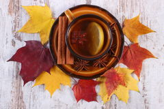 Cup of tea with lemon, spices and autumnal leaves on wooden background Stock Photo
