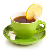 Cup of tea with lemon and sugar cubes on white bac. Green cup of tea with lemon and sugar cubes Royalty Free Stock Photography