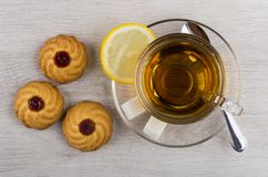 Cup of tea, lemon, sugar, teaspoon and cookies with jam. On wooden table Royalty Free Stock Image