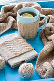 A cup of tea with lemon in sweater, old notebook. A cup of tea with lemon in sweater,  old notebook, beige knitted blanket and spokes lie on blue background Stock Photo