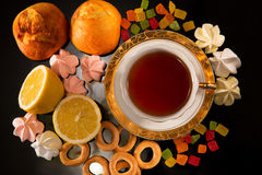 Cup of tea with a lemon and sweets. Still life against a dark background Royalty Free Stock Images