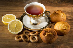 Cup of tea with a lemon and sweets. Still life against a dark background Royalty Free Stock Photos