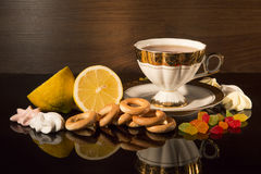 Cup of tea with a lemon and sweets. Still life against a dark background Royalty Free Stock Photography