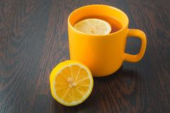 Cup of tea with lemon on table close-up. healthcare, traditional medicine and flu concept - tea cup with lemon. Hot tea with lemon, treatment of colds, flu and Royalty Free Stock Photos