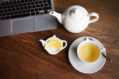 Cup of tea with lemon on table in modern cafe / restaurant / bar interior. Cup of green tea with honey and white pot on the  wooden table. Copy space area for Royalty Free Stock Photo