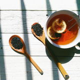 Cup of tea with lemon, tea in bulk on a wooden spoon on a white background.  Royalty Free Stock Photography