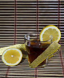 Cup of tea with a lemon wrapped up by a gold tape Royalty Free Stock Photo