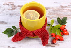 Cup of tea with lemon wrapped woolen scarf, warming beverage for flu, autumn decoration Royalty Free Stock Photography