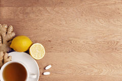 Cup of tea, lemons, ginger and two supplements pills on wooden background. Top view. Flat lay. Copy space for text Royalty Free Stock Images