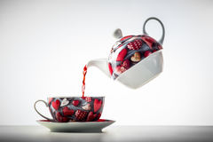 Cup of tea from levitating teapot stock image