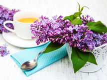 Cup of tea and lilac flowers Stock Photos