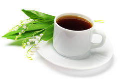 Cup of tea and lilies of the valley Stock Images