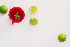 Cup of tea and limes. Pink cup of tea with mint leaf and green limes on white background Royalty Free Stock Photography