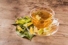 Cup of tea and linden on wooden background Royalty Free Stock Photography