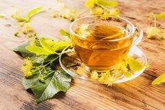 Cup of tea and linden on wooden background Royalty Free Stock Image