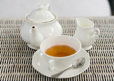 Cup of tea with little milk jar and teapot Stock Images