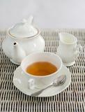 Cup of tea with little milk jar and teapot Stock Photos