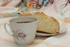 A cup of tea and loaf of bread. Tea in white porcelain cup with purple rose  and loaf of bread cutted on white plate on coloured tablecloth Stock Image