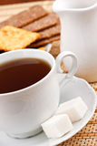 Cup of tea with a lump sugar and crackers. A cup of black tea with a lump sugar and crackers for breakfast stock photos