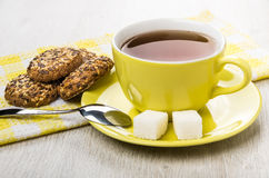 Cup of tea and lump sugar on saucer, cookies Stock Image