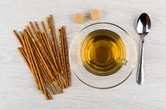 Cup of tea, lumpy sugar, salted breadsticks and teaspoon. On wooden table. Top view Stock Image