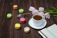 Cup of tea, macarons, glasses, pink tulips and notebook on woode Stock Photos