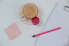 Cup of tea with macaroon, clipboard, pencil and sticky note Royalty Free Stock Images