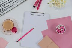 Cup of tea with macaroon, keyboard, diary, pebbles, flowers, clipboard, pencil and sticky note Royalty Free Stock Photography