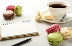 Cup of  tea with macaroоns and notebook . Stock Photos