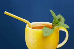 A cup of tea made from natural lemon with mint leaves. Creative composition on the theme of natural tea Stock Images