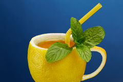 A cup of tea made from natural lemon with mint leaves. Creative composition on the theme of natural tea.  Royalty Free Stock Photos