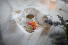 Cup of tea and marmalade in a jar lay in the cart covered with a white silk cloth royalty free stock image