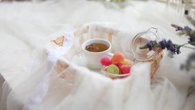 Cup of tea and marmalade in a jar lay in the cart covered with a white silk cloth. A Cup of tea and colored marmalade in a jar lay in the cart covered with a stock video