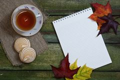 Notepad and a cup of tea with marshmallows on an old wooden table. Autumn background. View from above. A cup of tea with marshmallows, a notebook and maple Royalty Free Stock Photos
