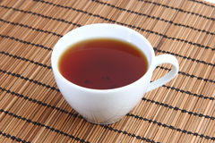 Cup of tea on the Mat. White cup of tea on the Mat Royalty Free Stock Image