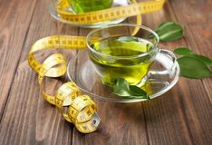 Cup of tea and measuring tape on wooden table. Weight loss concept Stock Image