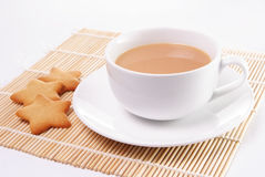 Cup of tea with milk. And star shaped biscuits Stock Image