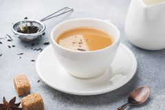 Cup of tea with milk, brown anise sugar on a grey table.  royalty free stock photo