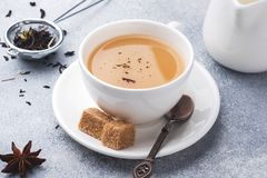 Cup of tea with milk, brown anise sugar on a grey table.  stock image