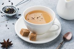 Cup of tea with milk, brown anise sugar on a grey table.  royalty free stock images