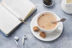 Cup of tea with milk, brown anise sugar and a notebook on a grey table.  stock photos