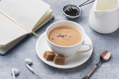 Cup of tea with milk, brown anise sugar and a notebook on a grey table.  stock image
