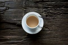 Cup of tea with milk or coffee on table with wooden damaged surface. Grunge texture of breakfast table Stock Photos
